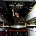 Ouvrier dans fosse de visite effectuant la vidange d'un autobus au centre bus de Lagny